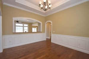 Formal dining room of this Glendale model features wainscotting and a treyed ceiling