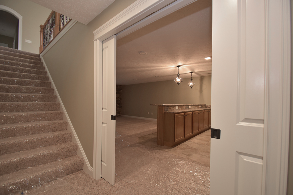 Landing of basement features double pocket doors of living space in lower level