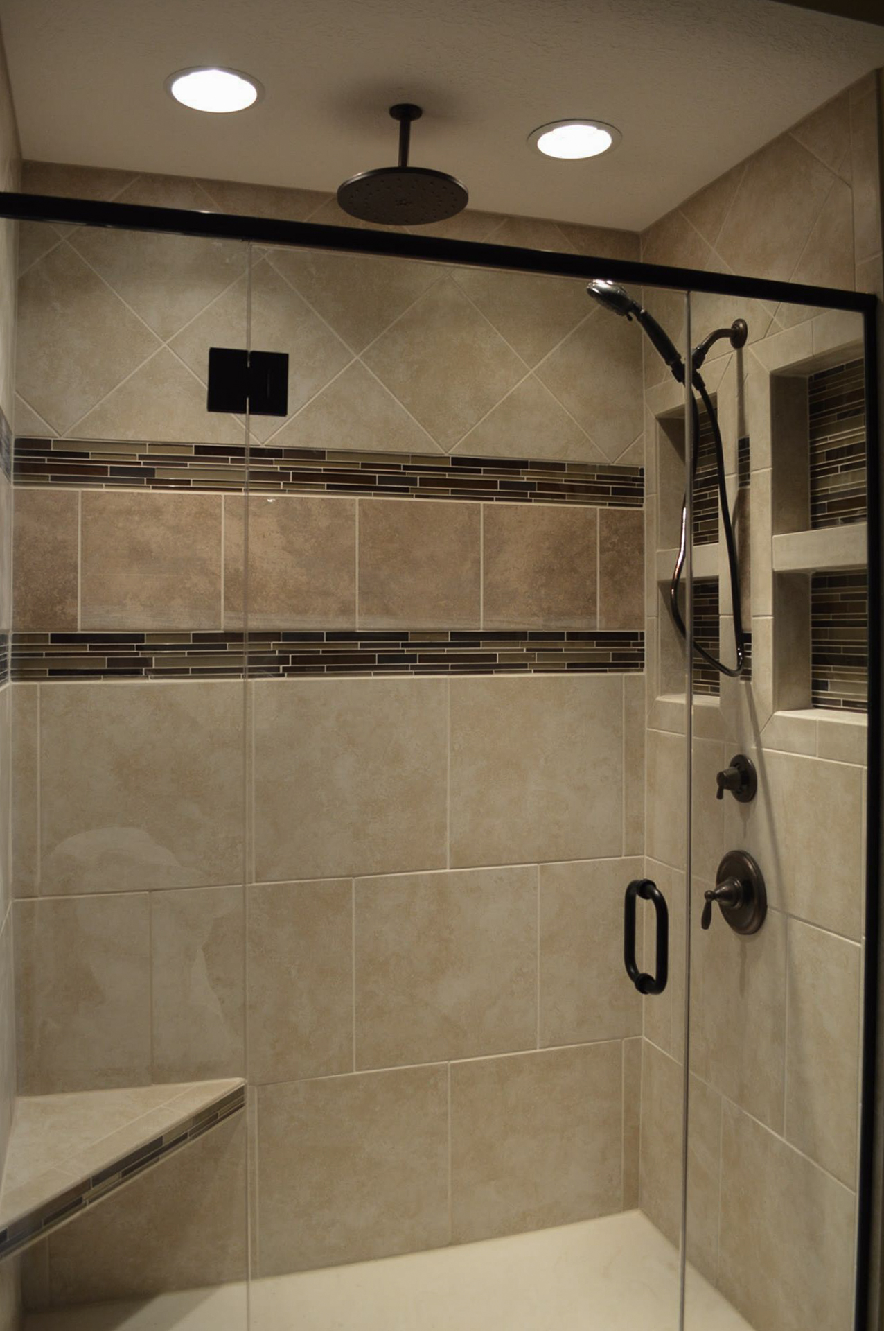 Ceramic tile shower with recessed boxes and seat with Brantford ORB fixture