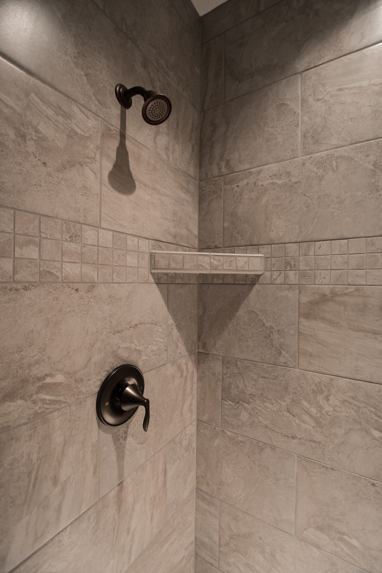 Custom floor-to-ceiling ceramic shower with 2 shelves and a seat, Moen T2132 oil rubbed bronze fixture