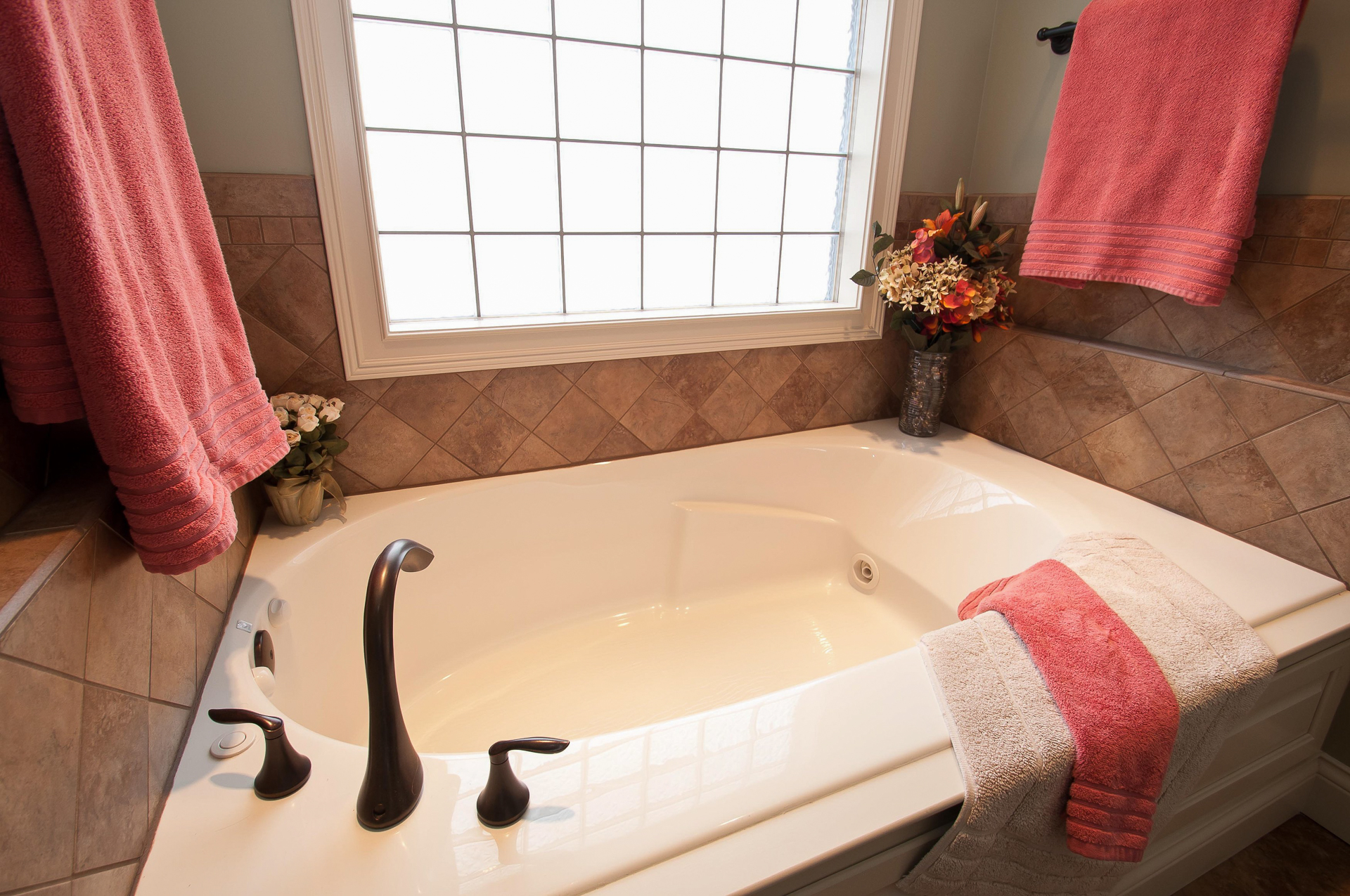 Soaking tub with jets and Eva oil rubbed bronze faucet, surrounded by ceramic tile