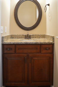Powder room with granite tops and round framed mirror