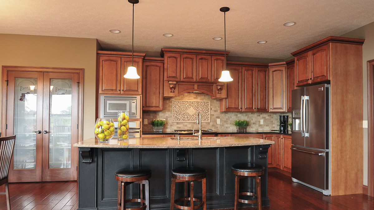 Kitchen Of Glendale Model Features Medium Stained Wood Cabinets,  Contrasting Black Island, Granite Countertops