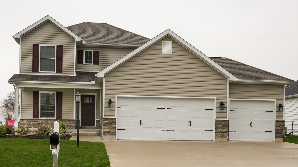 Saratoga model with porch features vinyl siding and stone built in Edgewater