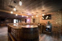 Bar area in basement is finished with real brick walls, wood planked ceiling, & an arcade area