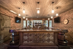 Bar area in basement is finished with real brick walls, wood planked ceiling, custom bar tops, whiskey barrel shelves, a dishwasher, wine chillers, ice maker and tap!