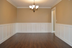 Dining room with Trinity bronze light fixture and wainscot trim