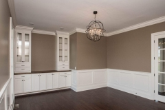 Formal dining room with glamorous light fixture, wainscot trim and custom built-ins