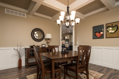 Dining room in this Berkshire model features coffered ceilings and wainscotting with Arden light fixture