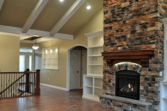 Great room of Allison model features cathedral ceiling with painted ceiling beams, floor-to-ceiling fireplace with Sienna drystack stone, and flanking built ins