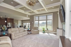 Custom home great room includes 12' coffered ceilings, custom built in that flank center focal point and LED fireplace