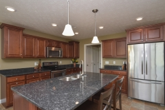 Kitchen of Bristol model in medium stained cabinets and granite countertops, Keats light fixtures