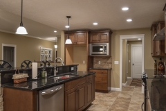 Kitchen of Allison model features medium stained wood cabinets, black granite and travertine backsplash, Madison light fixtures