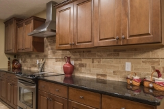 Kitchen of Allison model features medium stained wood cabinets, black granite and travertine backsplash
