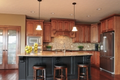Kitchen of Glendale model features medium stained wood cabinets, contrasting black island, granite countertops and travertine backsplash