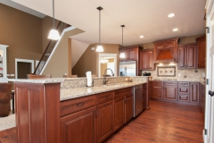 Kitchen of modified Belmont model features medium stained cabinets, granite countertops and travertine backsplash, North Park light fixtures