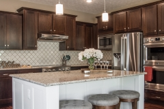 Kitchen of custom built home features Echelon Maple Norwich Linen for island only. Norwich Espresso for the rest of kitchen. Giallo Ornamental granite and decorative backsplash, Alexa light fixtures