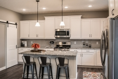 Kitchen of Arlington model features white cabinets and island, subway ceramic tile backsplash, and granite countertops, Bravo light fixtures