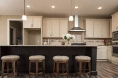 Kitchen of Berkshire model features Shamrock shaker cabinets in taupe - island in java, new venetian gold granite countertops and travertine backsplash, Arden light fixtures