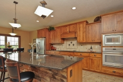 Kitchen of Excalibur model features rustic stained cabinets, granite countertops, and Sienna stone on the island, North Park light fixtures