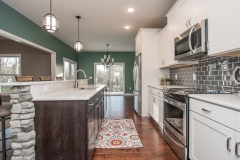 Kitchen of custom built home with white cabinets, quartz countertops and subway pattern backsplash, Bay Court light fixtures on island, Wisten light fixture in dining