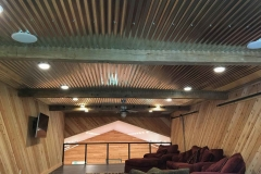 Loft / sitting area of basketball court with galvanized tin roof, wood beams, and tongue & groove pine walls