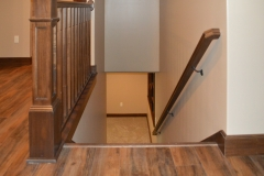 Stained railings and flat-panel box newel posts, stained skirtboards, stained square-chamfer balusters