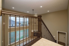 Stained handrail and box newels with iron ballusters: plain, plain, double-knuckle pattern