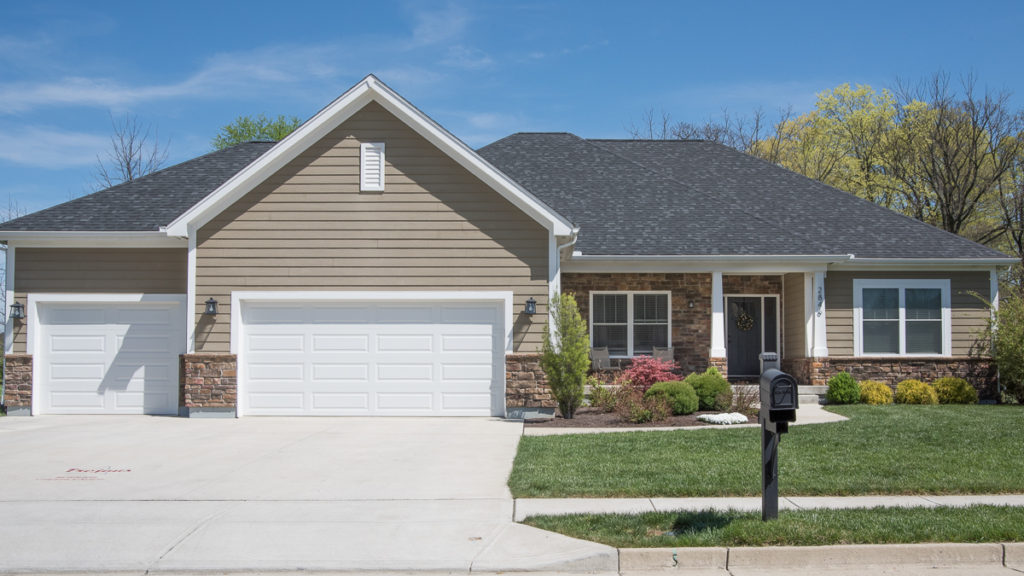 Custom built home with LP painted siding and stone exterior features 3 car garage with white long panel garage doors