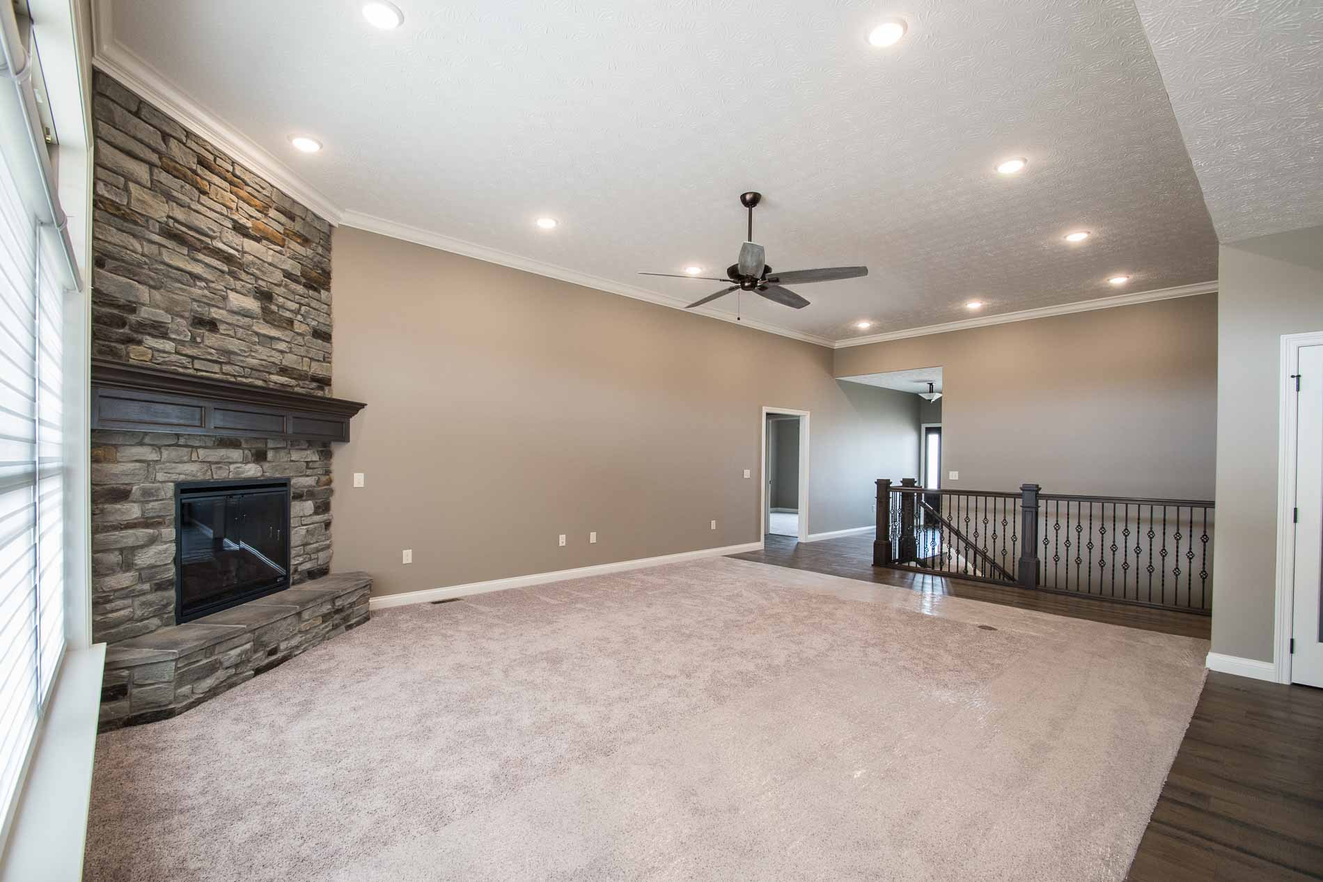 Great room of Allison model with corner stone fireplace