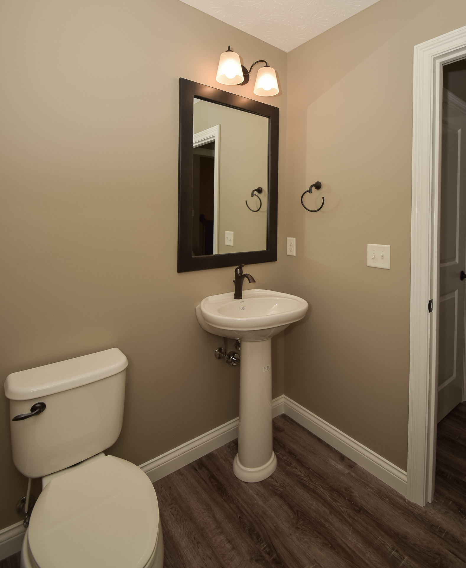 Mansfield Waverly 340 pedestal sink in biscuit with Eva ORB fixure, Arden light fixture
