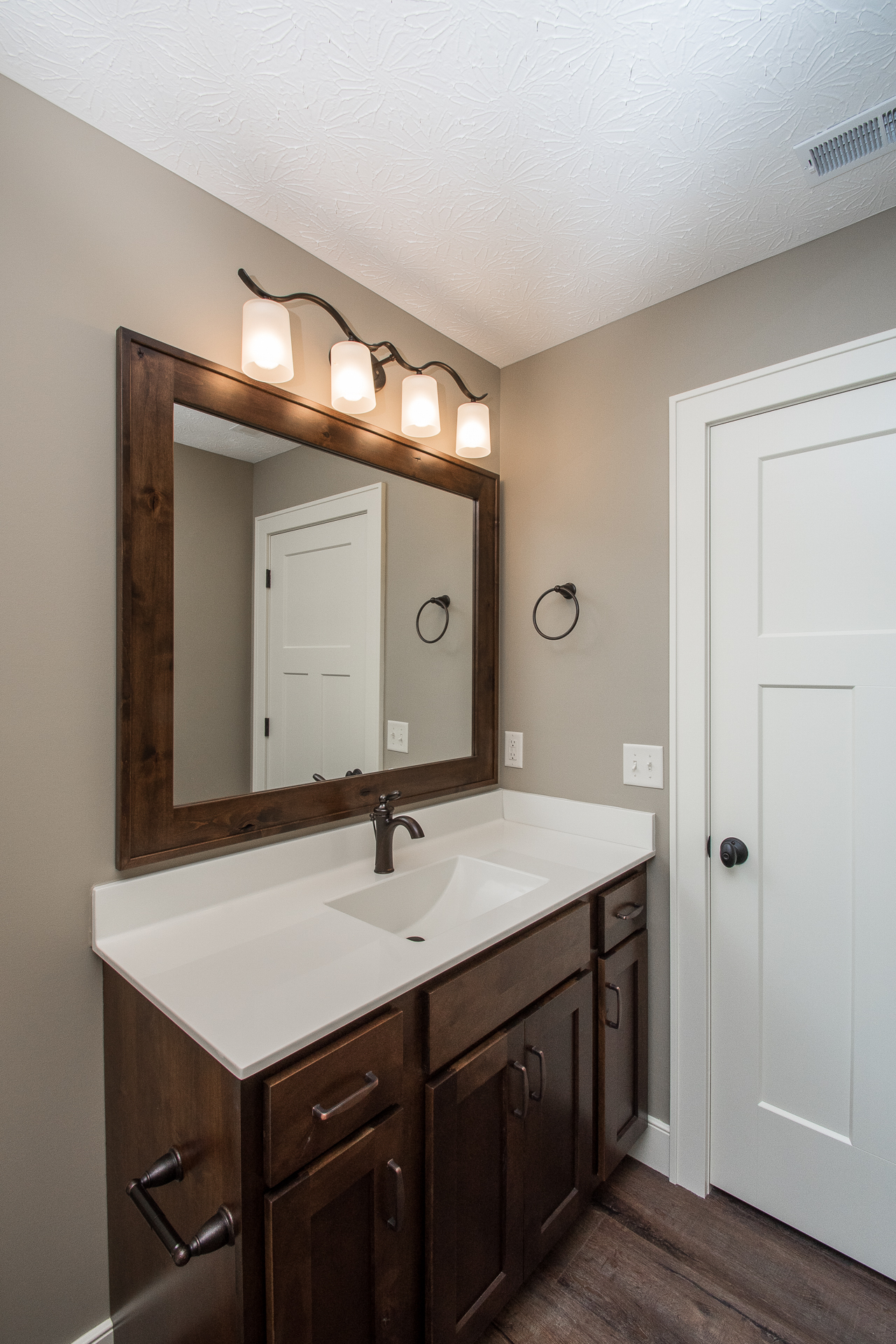 Rustic Birch Windsor in Mocha cabinets with one-pc cultured marble top in #43 biscuit features wave bowl and Brantford oil rubbed bronze faucet
