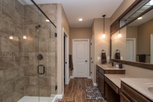 Oxford Birch mocha cabinets, one-pc cultured marble tops in #115S Goldenrod, recessed oval bowl, ceramic tile shower, Brantford oil rubbed bronze faucet