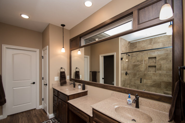 Oxford Birch mocha cabinets, one-pc cultured marble tops in #115S Goldenrod, recessed oval bowl, ceramic tile shower