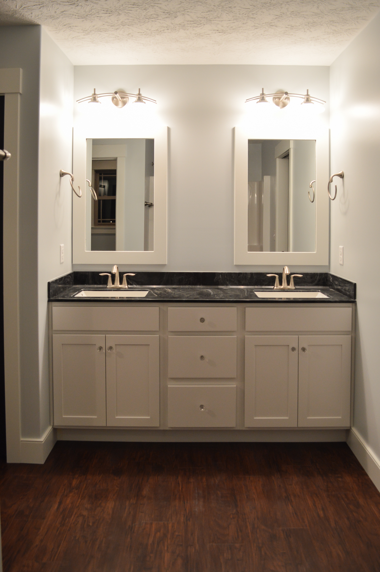 Double vanity with white cabinets, cultured marble top, framed mirrors, and brushed nickel Eva faucets