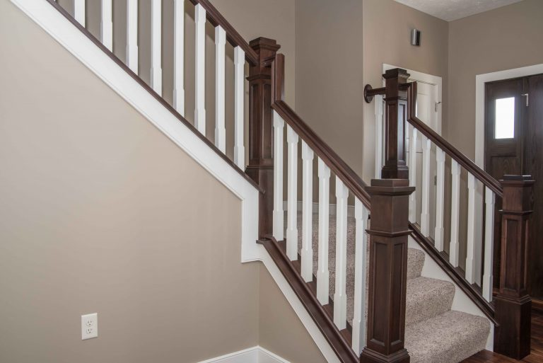 Stained railings and flat panel box newel posts with painted chamfered-square balusters