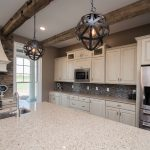 Custom painted cabinets with glaze for perimeter, #76023 Baymont Maple for island cabinets, perimeter quartz tops in Las Medulas Q4016, quartz island top in Paradise Cove CQ868, Sienna Ledge Stone behind range