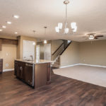Great Room in Saratoga model is open to kitchen and features corner fireplace