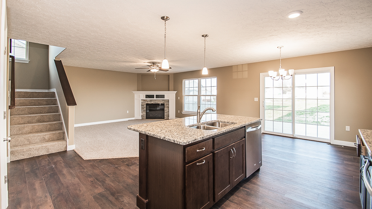 Great room in Saratoga model is open to the kitchen. Features corner fireplace