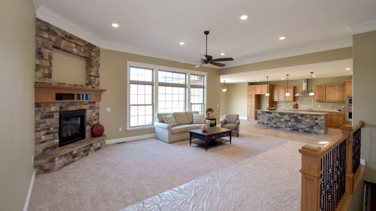 Great room of Glendale model features an 11' ceiling and a corner fireplace with Sienna Drystack stone