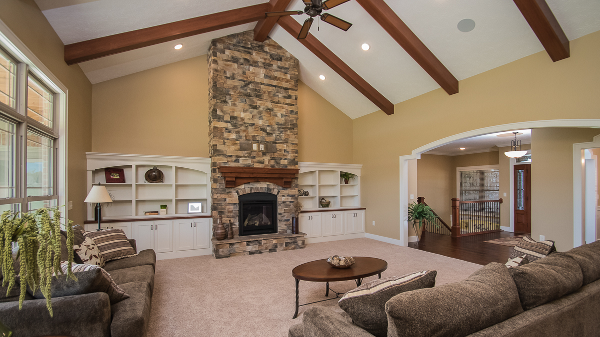 Barrington great room features 11' walls with wood beams on cathedral ceiling, floor to ceiling stoned fireplace (Sienna Dry Stack) and flanking built ins