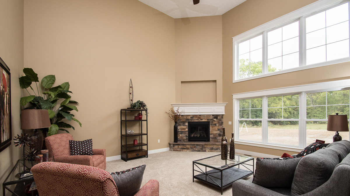 2 Story Great Room of Windmill model features center fireplace with raised hearth and Sienna stone. TV peripherals are conveniently located in hidden painted mantel