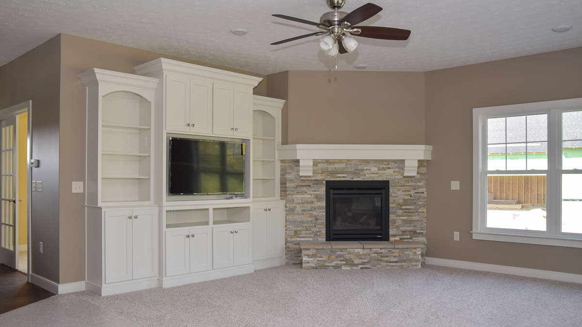 Great room of a custom built home features corner fireplace with stone accent and entertainment built ins