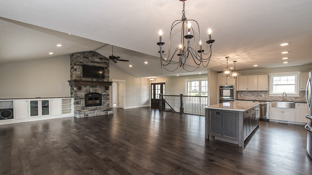 Great room and kitchen is wide open in this custom built home. Floor-to-ceiling wood burning fireplace is accompanied by custom built ins.