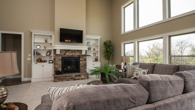 2 Story Great Room of Berkshire model features Sienna stone-accented fireplace with painted flanking built ins