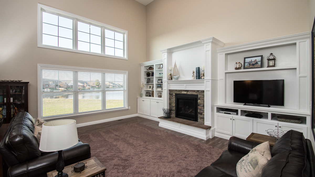 Great room in Windmill model features 2 story ceiling, custom built ins, and center fireplace