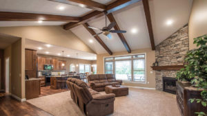 Great room of Allison model features cathedral ceilings with wood beams and corner floor-to-ceiling fireplace with natural blend ledge stone