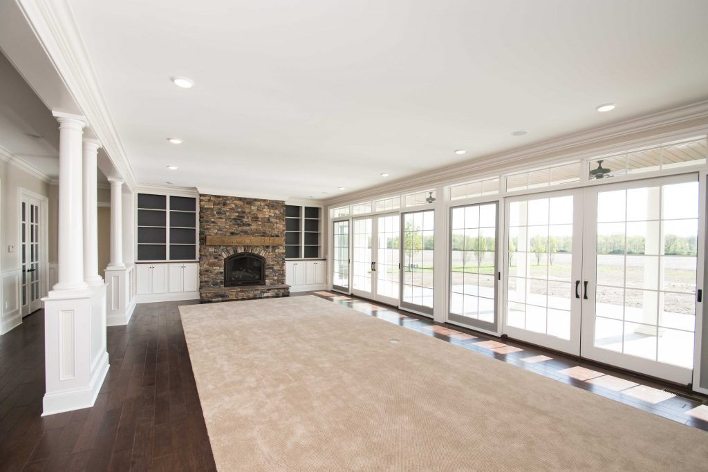 Great room of custom built home features Sienna Ledgestone on propane fireplace and carpet bordered by engineered hardwood - Andersen Eagle Lodge Plank Maple Lariat