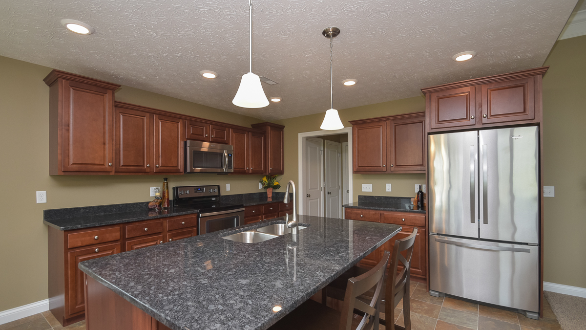 Kitchen of Bristol model in medium stained cabinets and granite countertops