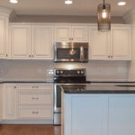 Kitchen of custom built home features white cabinets, white subway tile with white grout, and granite countertops